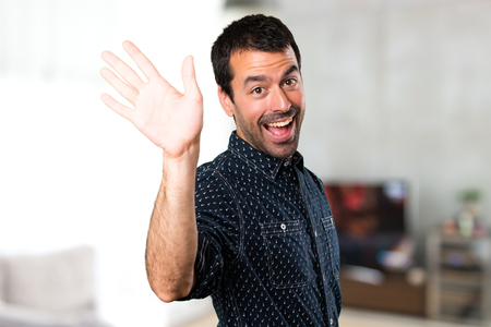 Photo for Brunette man saluting inside house - Royalty Free Image