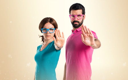 Photo pour Couple in colorful clothes making stop sign - image libre de droit