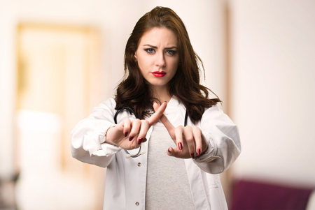 Doctor woman making NO gesture on unfocused background