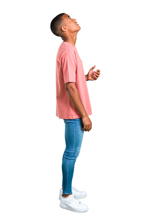 Foto de Standing young african american man stand and looking up on isolated white background. Ideal for use in architectural designs - Imagen libre de derechos