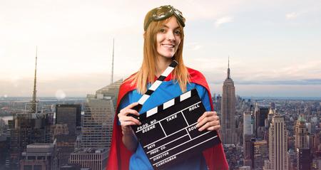 Pretty superhero girl holding a clapperboard in a skyscraper city