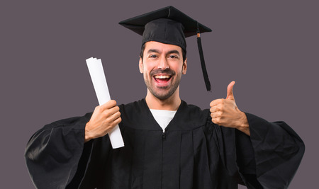 Photo pour Man on his graduation day University giving a thumbs up gesture and smiling because has had success on violet background - image libre de droit