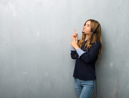 Photo pour Telemarketer woman pointing with the index finger and looking up - image libre de droit