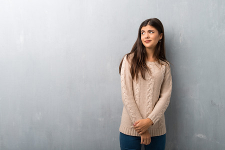 Teenager girl with sweater on a vintage wall is a little bit nervous and scared pressing the teeth