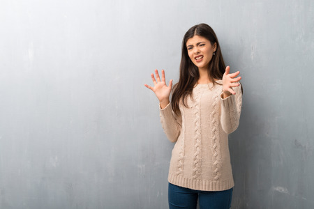 Teenager girl with sweater on a vintage wall is a little bit nervous and scared stretching hands to the front
