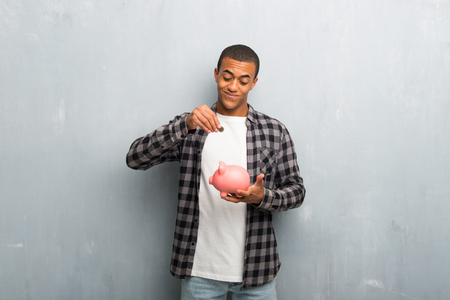 Photo pour Young african american man with checkered shirt taking a piggy bank and happy because it is full - image libre de droit