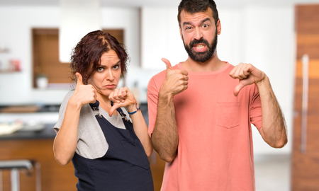 Photo pour Couple with pregnant woman making good-bad sign. Undecided between yes or not inside house - image libre de droit