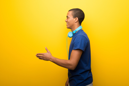 Photo for African american man with blue t-shirt on yellow background handshaking after good deal - Royalty Free Image