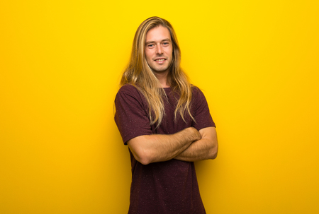 Foto de Blond man with long hair over yellow wall keeping the arms crossed in frontal position - Imagen libre de derechos