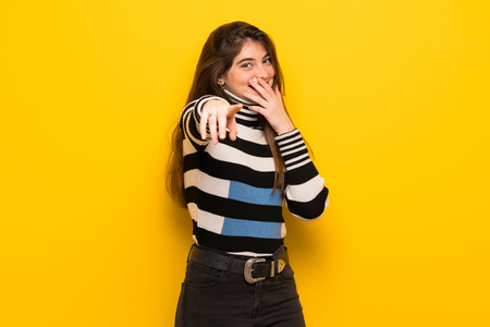 Photo pour Young woman over yellow wall pointing with finger at someone and laughing - image libre de droit