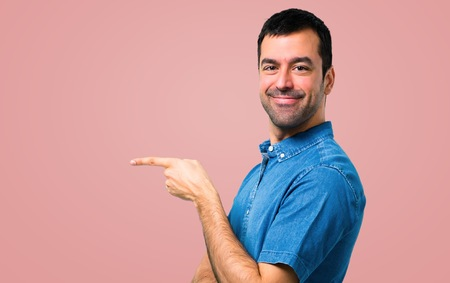 Photo for Handsome man with blue shirt pointing finger to the side and presenting a product on pink background - Royalty Free Image