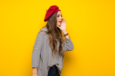 Foto de Girl with french style over yellow wall shouting with mouth wide open to the lateral - Imagen libre de derechos
