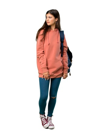 Foto de A full-length shot of a Teenager girl with sweatshirt and backpack feeling upset - Imagen libre de derechos