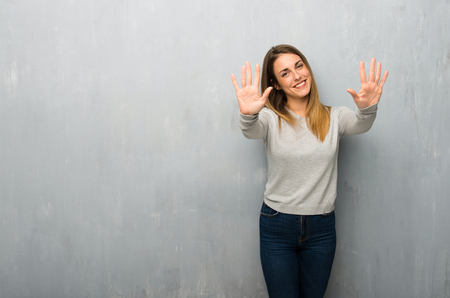 Photo pour Young woman on textured wall counting ten with fingers - image libre de droit
