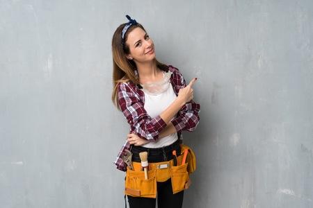 Foto de Craftsmen or electrician woman pointing back - Imagen libre de derechos