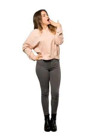 Photo for A full-length shot of a Teenager girl with pink sweater yawning and covering wide open mouth with hand over isolated white background - Royalty Free Image