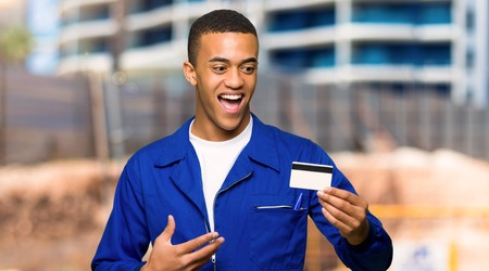 Photo pour Young afro american worker man holding a credit card and surprised in a construction site - image libre de droit
