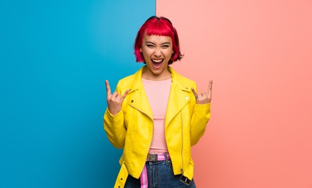 Photo pour Young woman with yellow jacket making rock gesture - image libre de droit