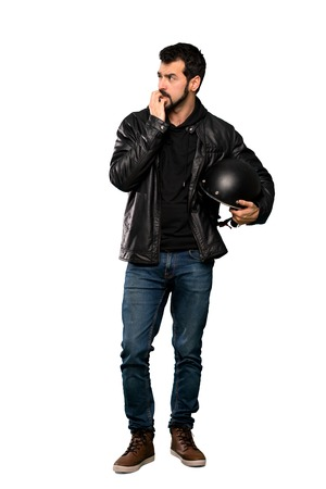 Photo pour Full-length shot of Biker man nervous and scared putting hands to mouth over isolated white background - image libre de droit