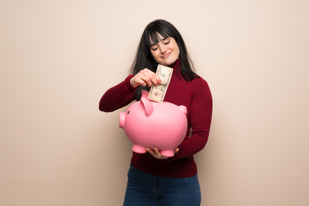 Photo pour Young woman with red turtleneck taking a piggy bank and happy because it is full - image libre de droit