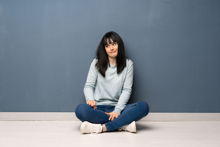 Photo for Woman sitting on the floor making doubts gesture looking side - Royalty Free Image