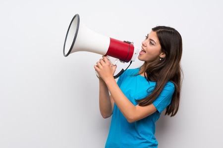 Photo for Teenager girl with blue shirt shouting through a megaphone - Royalty Free Image