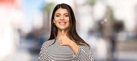 Photo pour Teenager girl with striped shirt with thumbs up because something good has happened at outdoors - image libre de droit