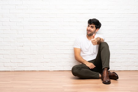 Photo pour Young man sitting on the floor with thumbs up because something good has happened - image libre de droit