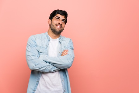 Photo pour Young man over pink wall looking up while smiling - image libre de droit