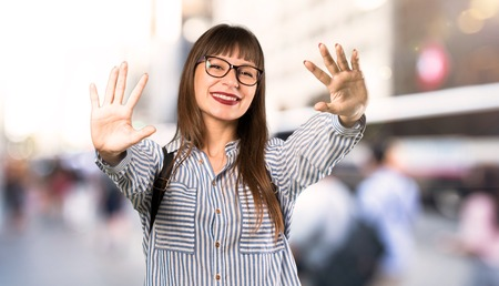 Photo pour Woman with glasses counting ten with fingers at outdoors - image libre de droit