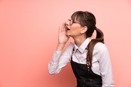 Photo for Young waitress over pink background shouting with mouth wide open - Royalty Free Image
