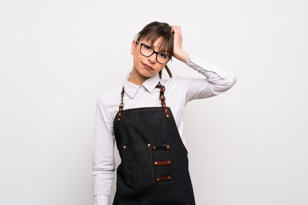 Foto de Young woman with apron with an expression of frustration and not understanding - Imagen libre de derechos