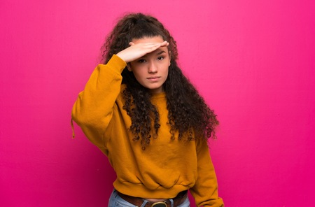 Photo pour Teenager girl over pink wall looking far away with hand to look something - image libre de droit