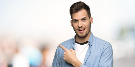Photo pour Handsome man pointing to the side to present a product at outdoors - image libre de droit