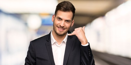Photo for Handsome business man making phone gesture. Call me back sign at indoors - Royalty Free Image