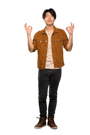 Foto de A full-length shot of a Asian man with brown jacket in zen pose over isolated white background - Imagen libre de derechos
