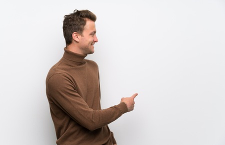 Photo pour Blonde man over isolated white wall pointing back with the index finger - image libre de droit