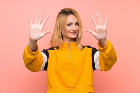 Photo pour Young blonde woman over isolated pink background counting ten with fingers - image libre de droit
