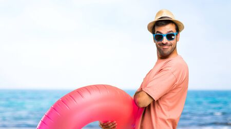 Foto de Man with hat and sunglasses on his summer vacation keeping the arms crossed in lateral position while smiling. Confident expression at the beach - Imagen libre de derechos