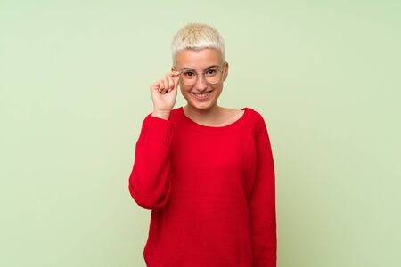 Foto de Teenager girl with white short hair over green wall with glasses and surprised - Imagen libre de derechos