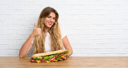 Photo for Young blonde woman holding a big sandwich with thumb up - Royalty Free Image