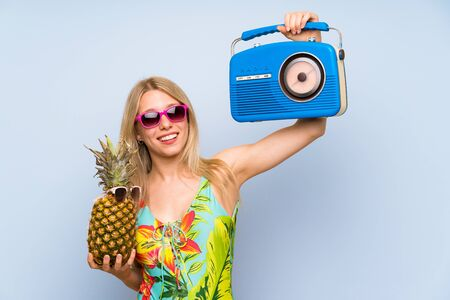 Photo for Young woman in swimsuit holding a pineapple with sunglasses and a radio - Royalty Free Image
