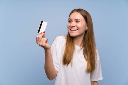 Photo pour Young woman over blue wall holding a credit card and thinking - image libre de droit
