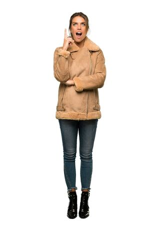 Photo pour A full-length shot of a Blonde woman with a coat pointing with the index finger a great idea over isolated white background - image libre de droit