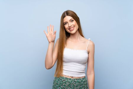 Foto per Young woman over isolated blue background saluting with hand with happy expression - Immagine Royalty Free