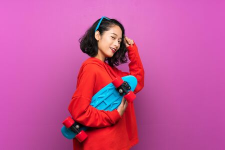 Foto de Asian young girl with skate over purple background - Imagen libre de derechos