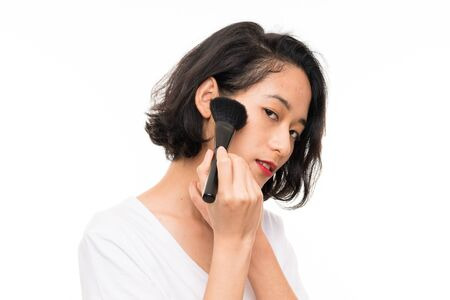Photo pour Asian young woman over isolated background with makeup brush - image libre de droit