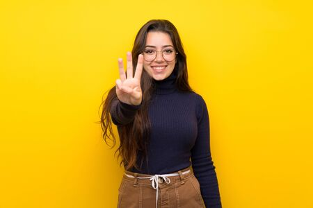 Photo pour Teenager girl over isolated yellow wall happy and counting three with fingers - image libre de droit
