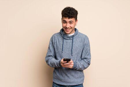 Foto de Young man over isolated wall sending a message with the mobile - Imagen libre de derechos