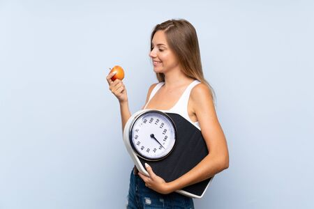 Foto de Young blonde girl with weighing machine and with an apple over isolated blue white background - Imagen libre de derechos